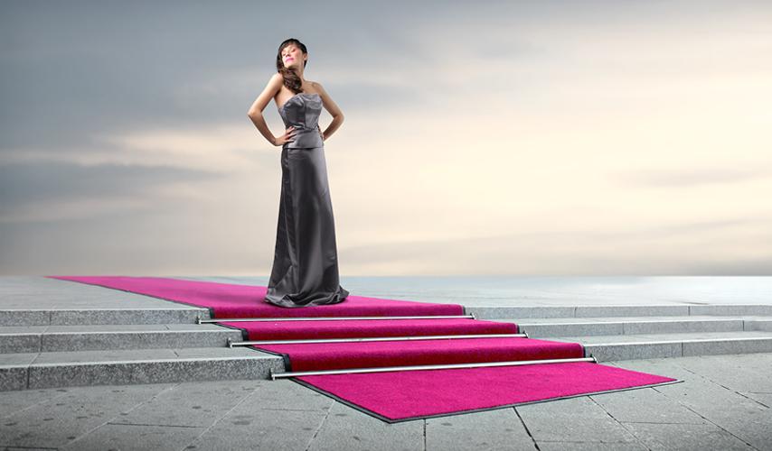 Cellstar Shootingfoto: Weibliches Model in einem silbernen langen Kleid steht auf einem langen, ausgerollten violetten Teppich